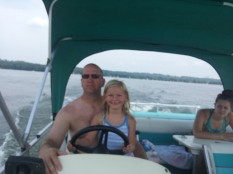Uncle Mike and Sophia drive the pontoon on Lake Minnewaska