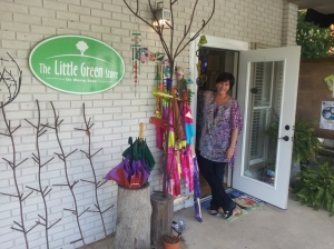 Ana Byrne, Ph.D., owner of The Little Green Store, peeks out on a recent Saturday.